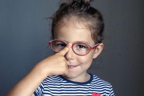 Menina ajustando os óculos.