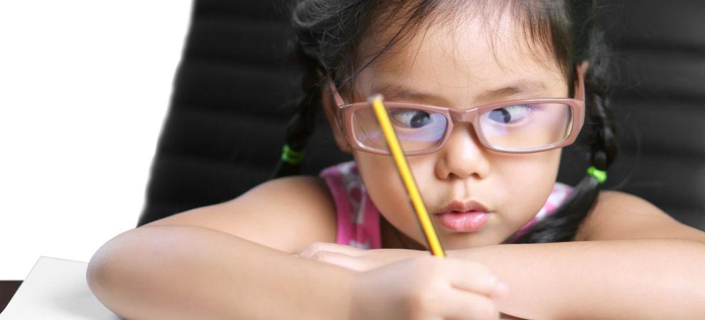 Menina com estrabismo estudando.